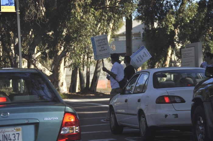 Picketers cross slowly, a few at a time, to hinder traffic