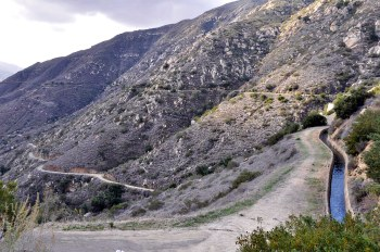 The concrete conduit snaking down the steep canyon below the dam. Access is from the service road below.