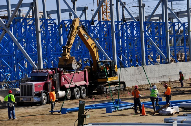 At Poseidon's Carlsbad desalination plant under construction, workers prepare a component for the reverse osmosis rack structure (blue) to be lifted by crane, while pipeline trenching goes on behind them.
